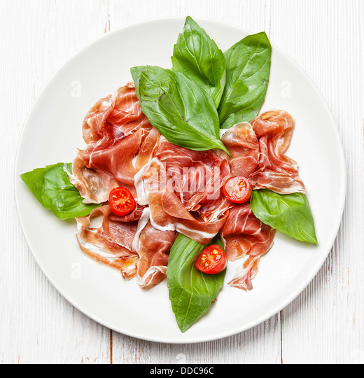 Plate of ham, tomato and basil - Stock Image