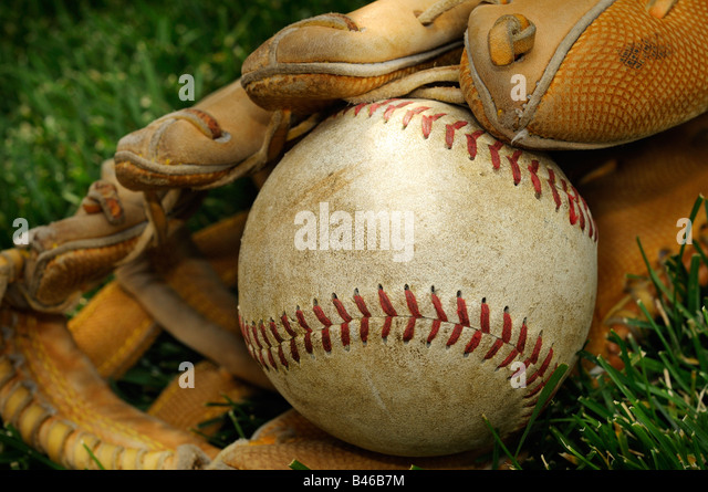 Old American Baseball And Leather Catchers Glove On A Grass Background - Stock Image