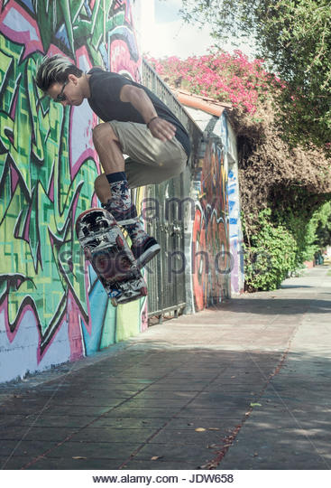 Young man doing jump on skateboard, mid air - Stock-Bilder