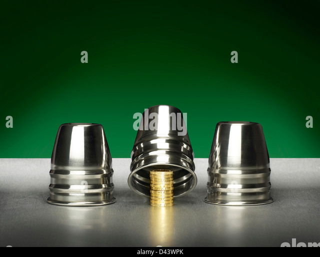 Three silver cups covering golden coins cut out green and silver background - Stock Image