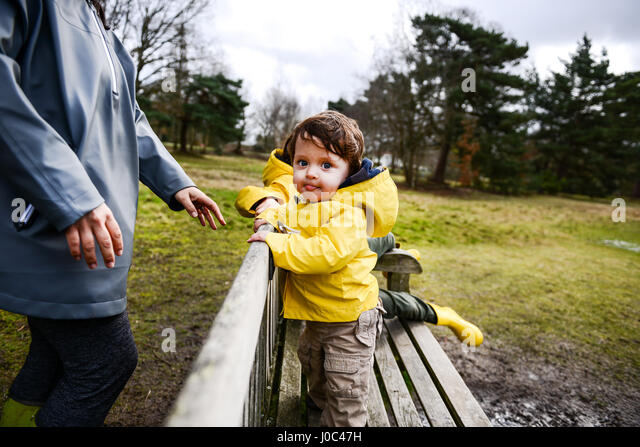 Baby boy with mother in yellow anorak on park bench - Stock Image