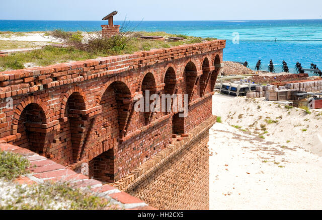 Brick laden corner parapet of Fort Jefferson looks out toward the decaying coaling dock pilings-Dry Tortugas, Florida - Stock Image