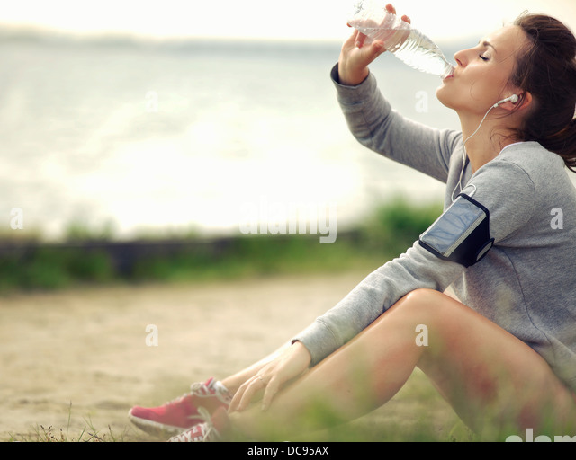 Female runner sitting on the grass while drinking water - Stock Image