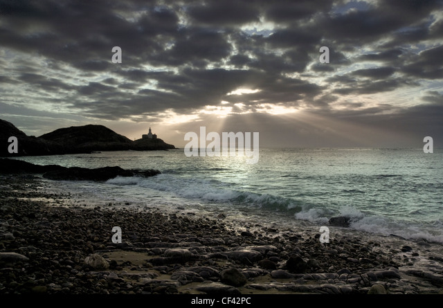 Rays of sunlight bursting through storm clouds over Mumbles Point at dawn. - Stock Image
