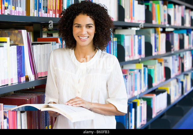 Woman in library holding book (depth of field) - Stock Image