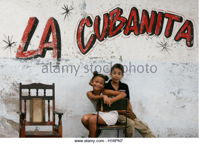 Cuban children sit on a chair on the street prior to a dancing parade in Santiago de Cuba, July 25, 2003. While - Stock Image