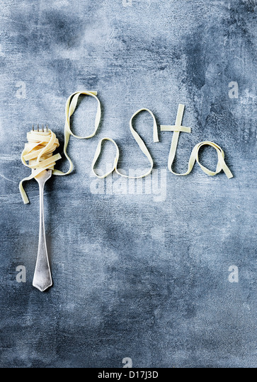 Fork with noodles spelling Pasta - Stock Image