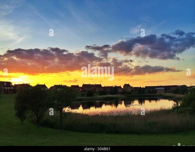 Houses overlooking lake at sunset, Hampton Vale, Peterborough, UK - Stock Image