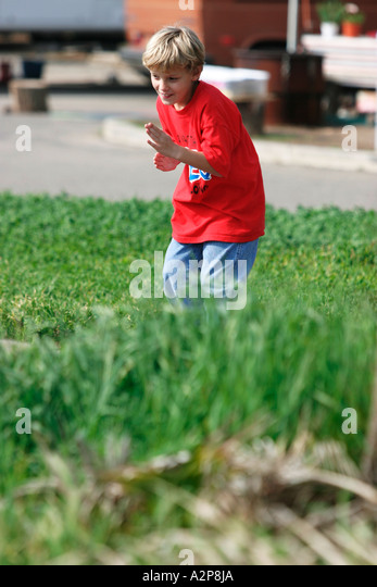 A young boy plays at the park. - Stock Image