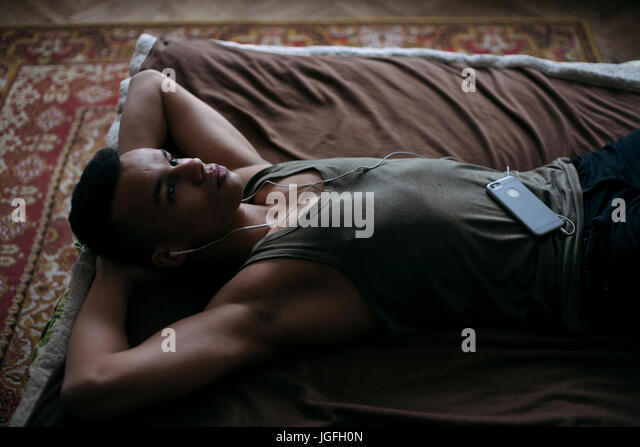 Black man laying on bed listening to music on cell phone - Stock Image