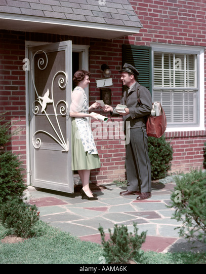 1950s MAILMAN DELIVERING MAIL TO WOMAN BRICK SUBURBAN HOME ALUMINUM SCREEN DOOR DELIVERY MAN HOUSEWIFE MAILBAG LETTER - Stock Image