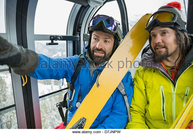 Male skiers talking in gondola in mountains - Stock-Bilder