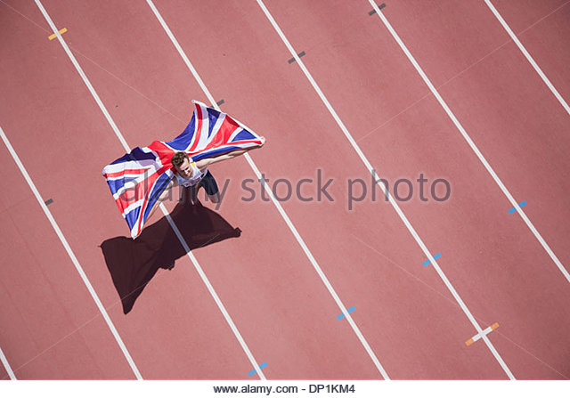 Runner celebrating with British flag on track - Stock Image