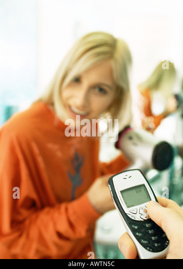 Man's hand holding cell phone, woman blow-drying hair in background - Stock Image