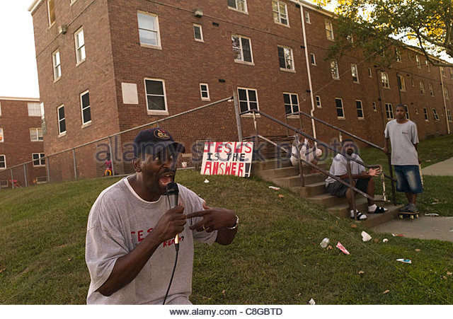 A minister preaching in a violent neighborhood. - Stock Image