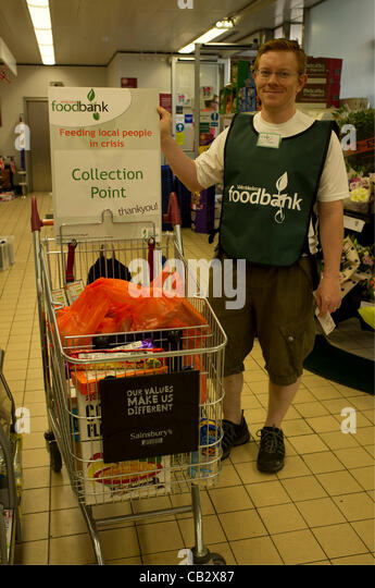 26 May, 2012. Wimbledon, London. Foodbank volunteer helps to collect food donations in a supermarket which will - Stock Image