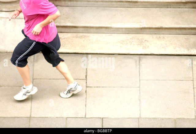 Royalty free photograph of woman running in her lunch hour on the pavement London UK - Stock-Bilder