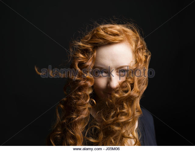Portrait woman with wind blowing long curly red hair - Stock Image