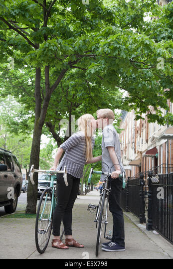 Young couple with bicycles kissing on street - Stock-Bilder