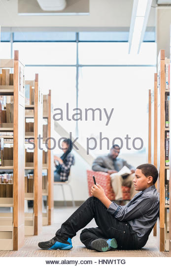 Teenage boy sitting on floor in library texting on cell phone - Stock-Bilder