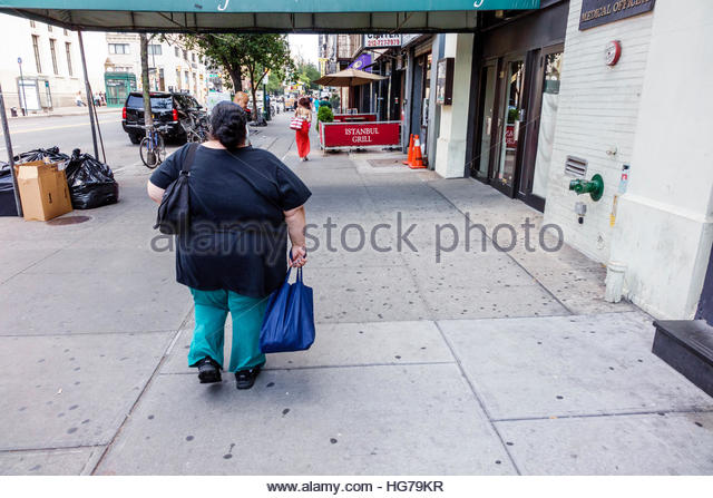 New York New York City NYC Manhattan Chelsea woman obese overweight walking sidewalk pedestrian - Stock Image