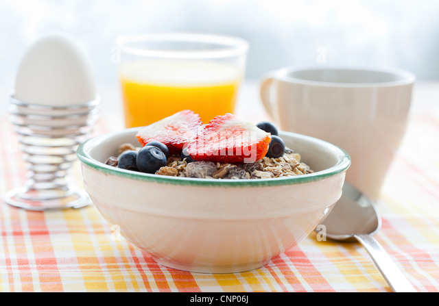 Bowl of muesli with strawberries and blueberries, boiled egg, orange juice and coffee for healthy breakfast - Stock Image