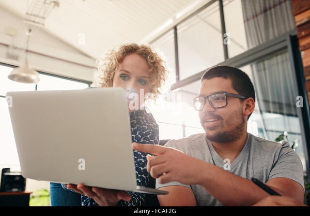 Two young graphic designers working in their own office. Man pointing at laptop in women's hands. - Stock Image