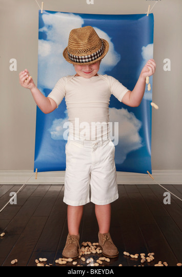 Boy in hat playing with peanuts in front of blue sky and clouds - Stock Image