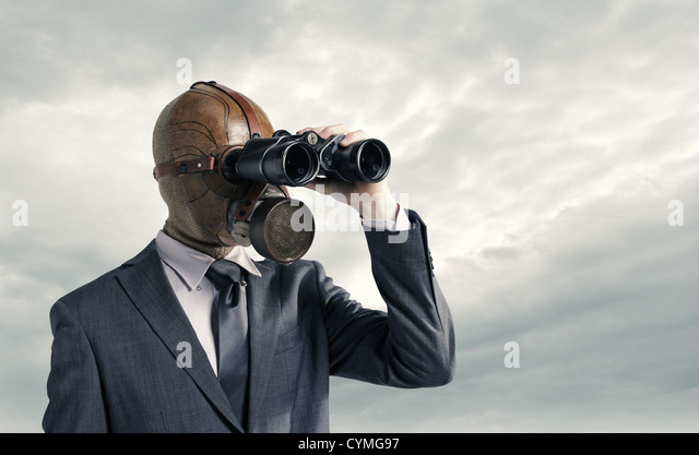Businessman with gas mask  looking through binoculars - Stock Image