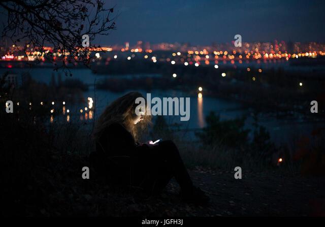 Caucasian woman standing near urban waterfront at night - Stock Image