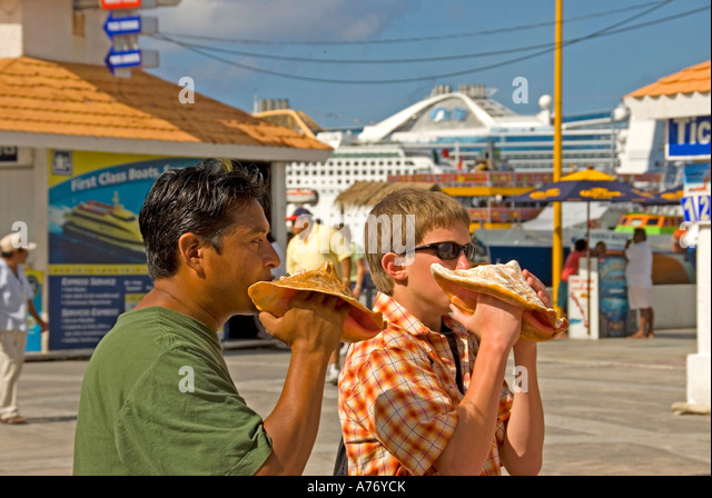 Cozumel Mexico San Miguel town learning to blow conch shell horn - Stock Image