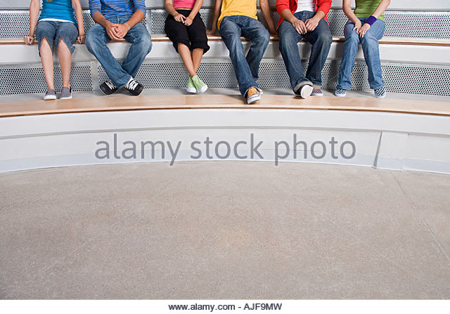 Young people sitting on a step - Stock Image