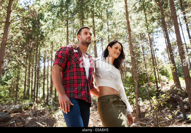 Young couple walking through forest, arm around - Stock-Bilder