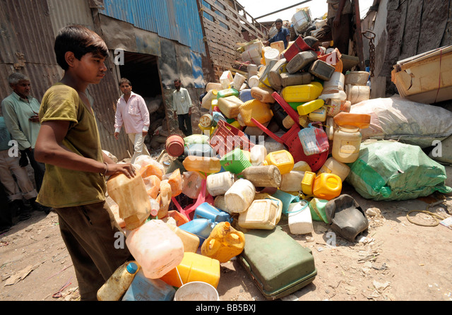 A young worker in Dharavi collecting and depositing plastic for recycling - Stock-Bilder