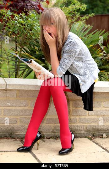 Teenage Girl Reading Magazine Model Released - Stock Image