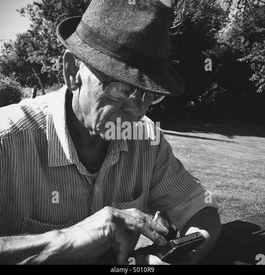Older man playing on smart phone - Stock Image