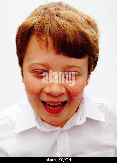 A happy 10-year old ginger haired boy - Stock Image