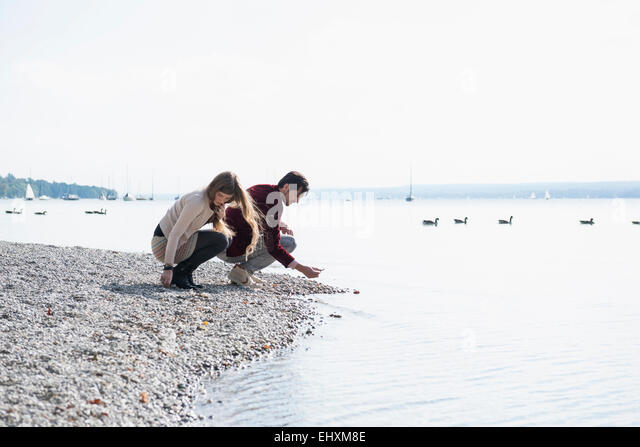 Young couple lake shore gathering pebbles - Stock Image