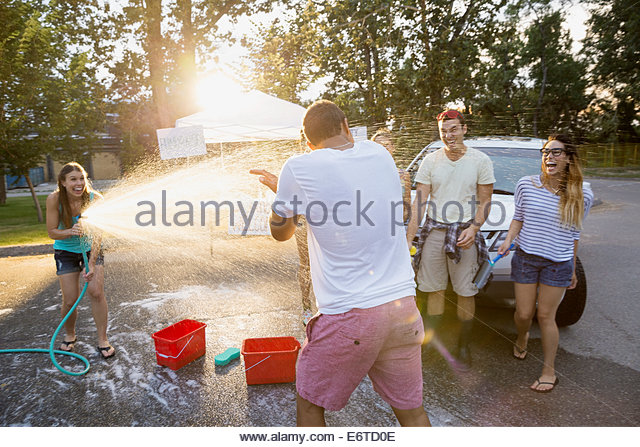 Woman spraying man with hose at car wash - Stock Image