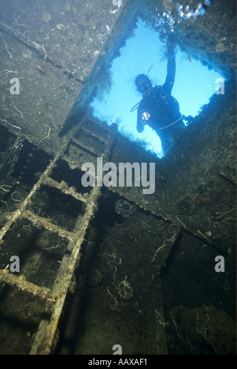 Diver exploring the hold of a ship wreck off the coast of Corsica - Stock Image