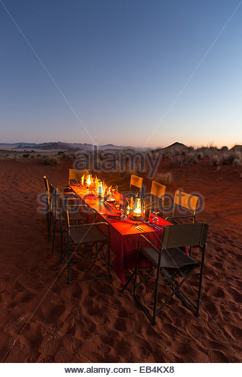 A romantic dinner table lit with lanterns in a desert landscape of scrub vegetation and low mountains. - Stock-Bilder