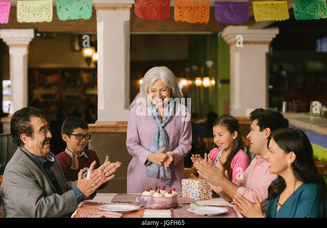 Family celebrating birthday of older woman in restaurant - Stock Image