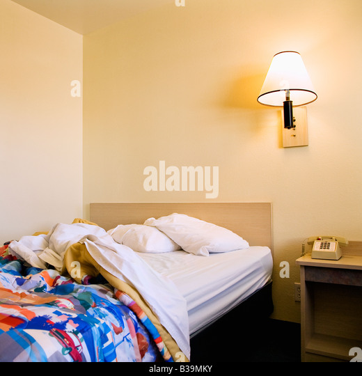 Interior shot of motel room with unmade bed and wall lamp - Stock Image