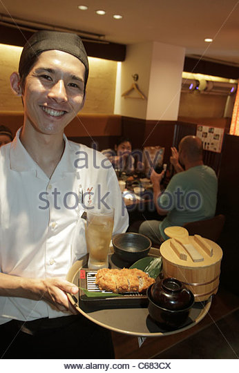 Tokyo Japan Ginza Chuo Dori Street restaurant Asian man waiter uniform smile interior server food drink tray - Stock Image