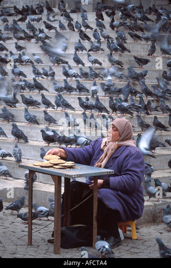 Turkey Istanbul Eminonu Square Muslim woman sells birdseed by Yeni Mosque steps pigeons - Stock Image