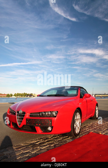 Red Alfa Romeo sports car with red carpet - Stock Image