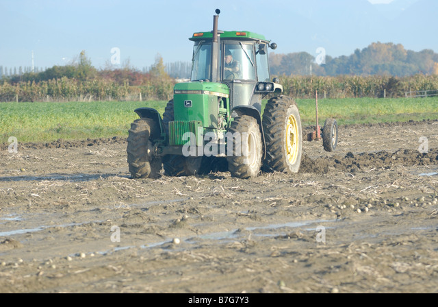 Farmer plowing his field With a Tractor. - Stock Image