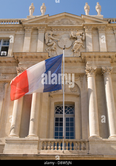 Detail of facade of the Marie (Town Hall) of Arles, France, with French flag and national crest with 'RF' - Stock Image