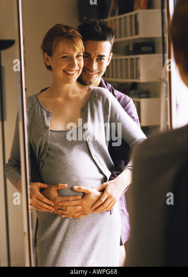 Man standing with arms around pregnant woman in front of mirror - Stock-Bilder