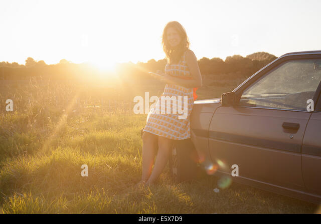 Portrait of mid adult woman leaning against car at sunset - Stock Image
